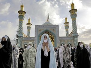 Worshippers wearing protective face masks offer Eid al-Fitr prayers outside a shrine to help prevent the spread of the coronavirus, in Tehran, Iran, Sunday, May 24, 2020. Muslims worldwide celebrated one of their biggest holidays under the long shadow of the coronavirus, with millions confined to their homes and others gripped by economic concerns during what is usually a festive time of shopping and celebration. (AP Photo/Ebrahim Noroozi)