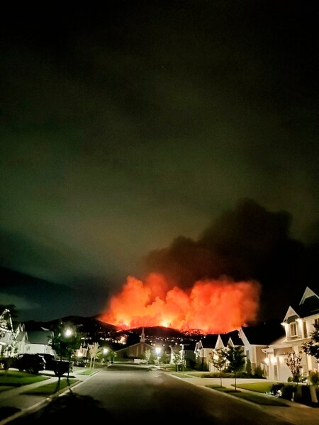 The Traverse Fire burns behind homes in Lehi, Utah, Sunday, June 28, 2020. Officials say fireworks caused the wildfire and forced evacuations early Sunday morning. (Justin Reeves via AP)