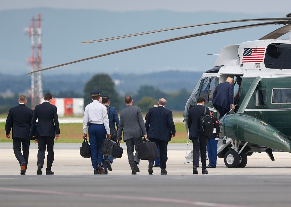 President Donald Trump, right, boards Marine One helicopter, followed by members of his staff at Hagerstown Regional Airport in Hagerstown, Md., Friday, Aug. 18, 2017, en route to nearby Camp David, for a meeting with his national security team to discuss strategy for South Asia, including India, Pakistan and the way forward in Afghanistan. (AP Photo/Pablo Martinez Monsivais)