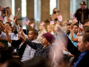 (Trent Nelson  |  The Salt Lake Tribune) Flags are waved to recognize fourteen new citizens at a naturalization ceremony that was part of Utah's World Refugee Week celebration, in Salt Lake City on Tuesday, June 15, 2021.