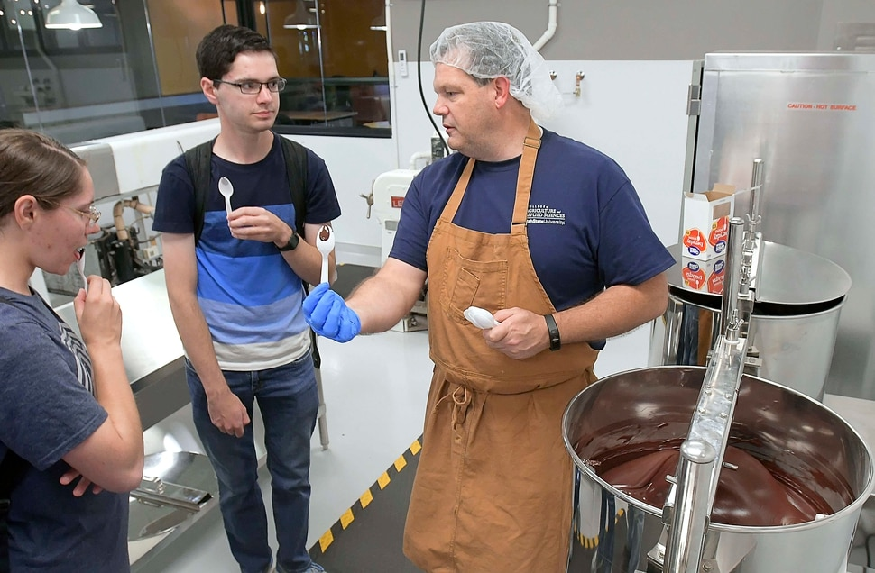 (Eli Lucero | The Herald Journal) Steve Shelton, right, talks to Akyra Winsor and Cameron Winsor while handing out samples during a public tour of the Aggie Chocolate Factory on Tuesday in Logan.