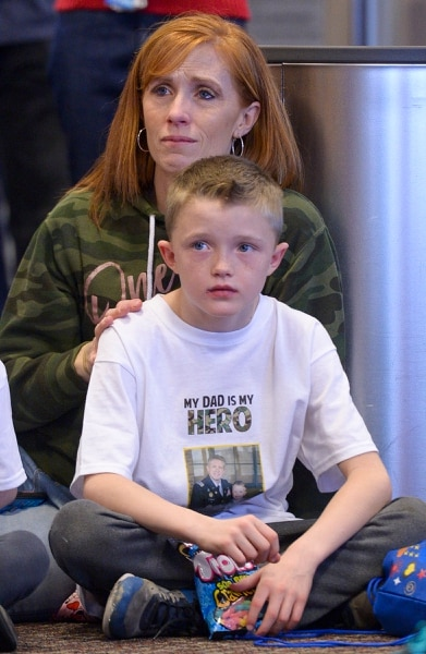 (Leah Hogsten | The Salt Lake Tribune) Jennie Taylor, the widow of Maj. Brent Taylor, and her son Jacob, watch a dance troupe before boarding their flight. Ten Gold Star families from Salt Lake City were treated to a Winter Wonderland scene, including Whoville and the Grinch at their boarding gate at Salt Lake International Airport, Dec. 7, 2019 before their flight to Disney World aboard the Snowball Express. This month, the Gary Sinise Foundation's Snowball Express will fly more than 1,700 family members of fallen U.S. military heroes to Disney World for a holiday retreat.