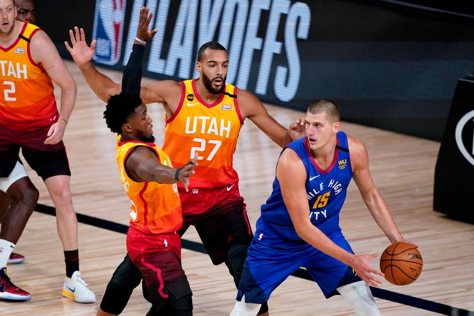 Denver Nuggets' Nikola Jokic (15) looks to pass under pressure from Utah Jazz's Rudy Gobert (27) and Donovan Mitchell during the first half of an NBA basketball first round playoff game Friday, Aug. 21, 2020, in Lake Buena Vista, Fla. (AP Photo/Ashley Landis, Pool)