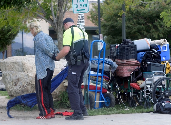(Al Hartmann   The Salt Lake Tribune) Salt Lake City Police check identifications and made arrests in a sweep of the Rio Grande neighborhood in downtown Salt Lake City Thursday September 29. Here they handcuff and search a woman on the block of 500 West between 300 and 400 South where many homeless spend time during the day in lawn chairs, sleeping bags and their suitcases.
