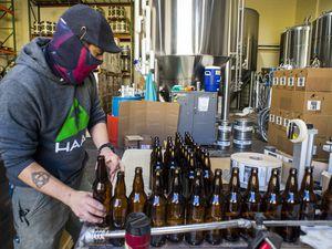 (Rick Egan     The Salt Lake Tribune)    Aaron Buckner loads bottles on the conveyer belt at Epic Brewing Co. in Salt Lake City, Thursday, Oct. 29, 2020.