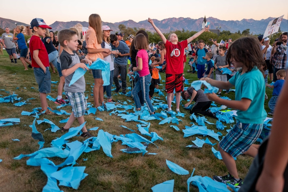 (Trent Nelson | The Salt Lake Tribune) Children rip up a large paper mask at a rally protesting government mask mandates at the State Capitol in Salt Lake City on Saturday, Sept. 5, 2020.