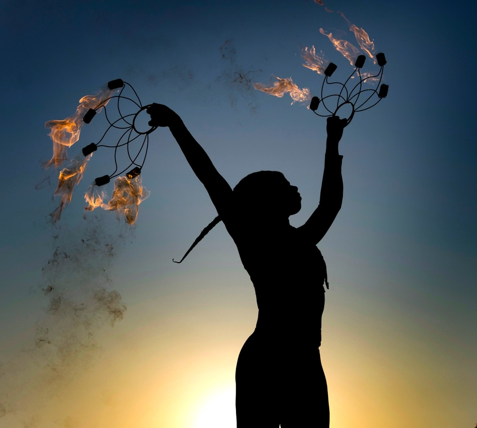 (Rick Egan | The Salt Lake Tribune) Tiana Powell from Rancho Cucamonga dances with fire at sunrise, during Burning Man, in the Black Rock Desert in Nevada, Saturday, Sept. 1, 2018.