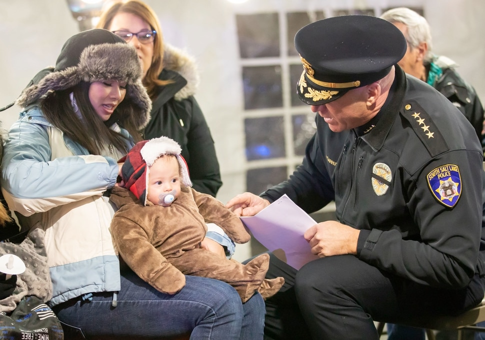 (Keith Johnson | Special to The Tribune) South Salt Lake Police Chief Jack Carruth talks to Liz Romrell and her son Jackson (4 months) before a candlelight vigil Dec. 2, 2018, at the Columbus Community Center in South Salt Lake for Liz's husband, fallen Officer David Romrell, a South Salt Lake police officer killed in the line of duty Nov. 24, when he was struck by a car driven by a fleeing suspect. Several hundred members of the community attended the vigil including family, friends, South Salt Lake Mayor Cherie Wood and representatives from the Utah Highway Patrol, Unified Police and Unified Fire.