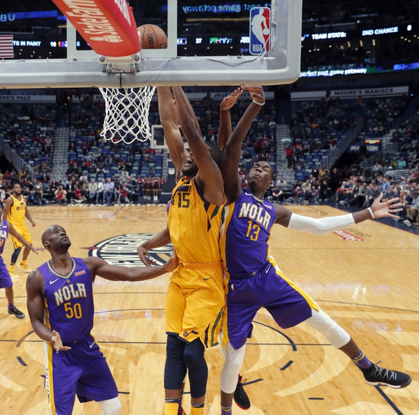 Utah Jazz forward Derrick Favors (15) goes to the basket between New Orleans Pelicans forward Cheick Diallo (13) and center Emeka Okafor (50) in the first half of an NBA basketball game in New Orleans, Monday, Feb. 5, 2018. (AP Photo/Gerald Herbert)