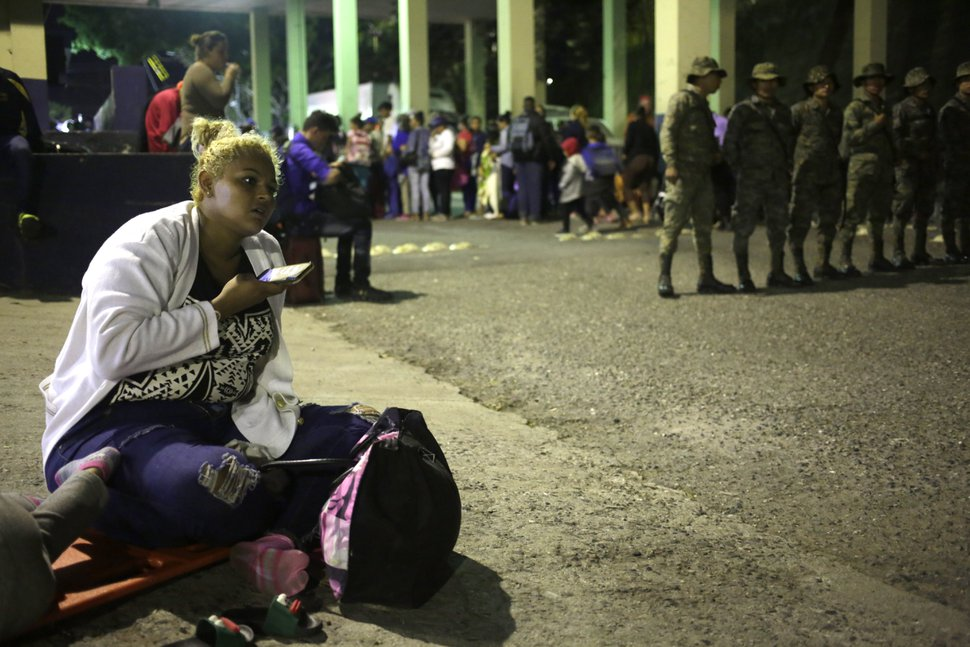 A Honduran migrant listens to her mobile phone while waiting to enter Guatemala, at the border crossing in Agua Caliente, Guatemala, Tuesday, Jan. 15, 2019. The latest caravan of Honduran migrants hoping to reach the U.S. has crossed peacefully into Guatemala, under the watchful eyes of about 200 Guatemalan police and soldiers. (AP Photo/Moises Castillo)