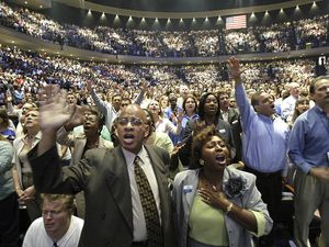 (Jessica Kourkounis   AP file photo) In this July 16, 2005, file photo, members of the Lakewood Church worship at the grand opening of their megachurch in Houston.