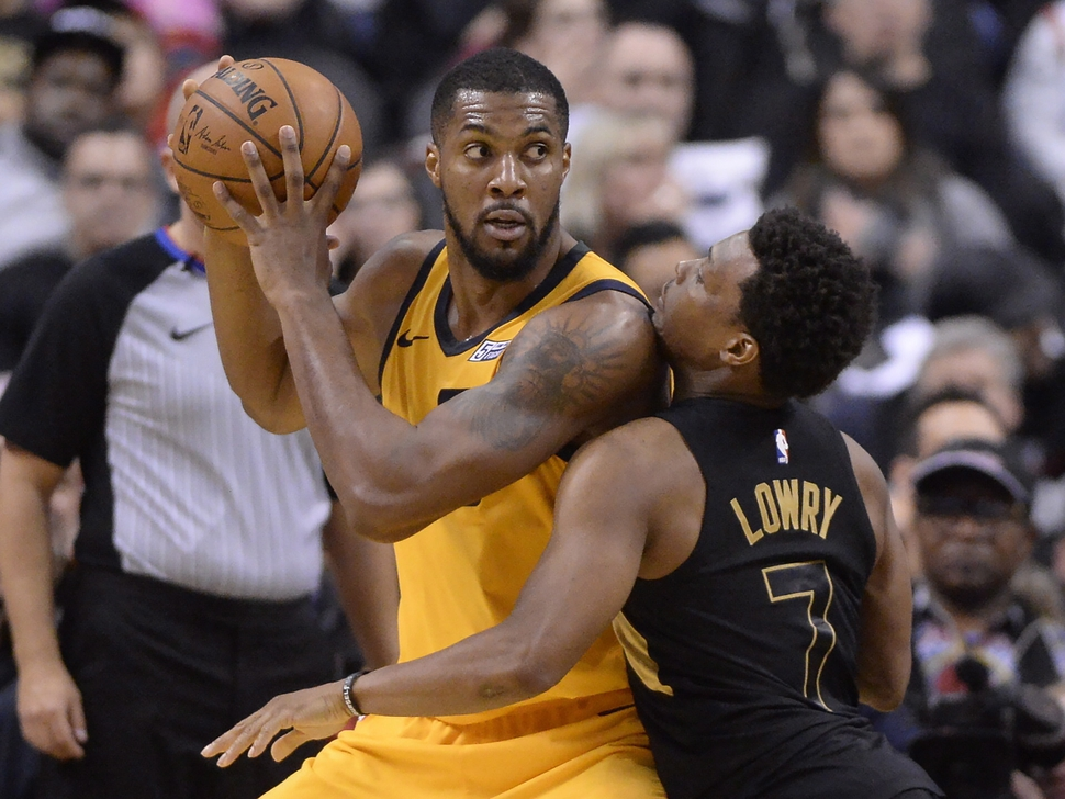 Utah Jazz forward Derrick Favors looks to pass as Toronto Raptors guard Kyle Lowry (7) defends during the second half of an NBA basketball game Friday, Jan. 26, 2018, in Toronto. (Frank Gunn/The Canadian Press via AP)