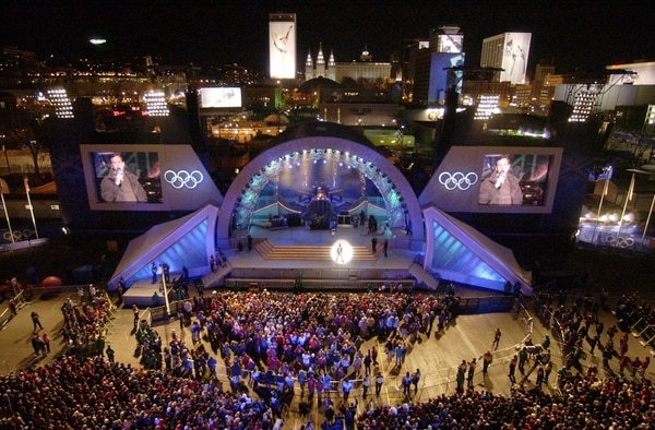 (Steve Griffin | Tribune file photo) With downtown Salt Lake City in the background, people surround the stage at the Olympics Medals Plaza during the opening night of the downtown venue Feb. 9, 2002.