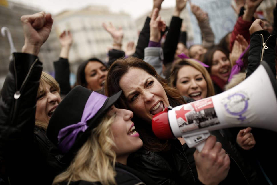 People, mostly women, shout slogans during a protest at the Sol square during the International Women's Day in Madrid, Thursday, March 8, 2018. Spanish women are marking International Women's Day with the first-ever full day strike and dozens of protests across the country against wage gap and gender violence. (AP Photo/Francisco Seco)