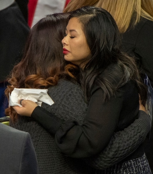 (Rick Egan | The Salt Lake Tribune) Elizabeth Romrell, wife of South Salt Lake police officer, David Romrell gets a hug, before the funeral at the Maverik Center, in West Valley City, Wednesday, Dec. 5, 2018.