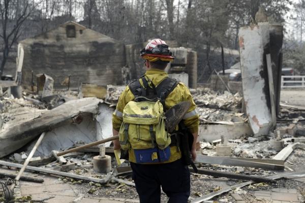 Capt. Scott Fisher, with the San Bernardino County Fire Department, surveys a wildfire-damaged neighborhood, Sunday, July 29, 2018, in Keswick, Calif. (AP Photo/Marcio Jose Sanchez)