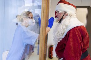 (Jens Buettner/dpa via AP)  In this Dec. 21 photo, Tessa Boulton, left, takes a swab test from Michael Kruse, dressed as Santa Claus, at a coronavirus testing center at the Helios Clinic in Schwerin, Germany.