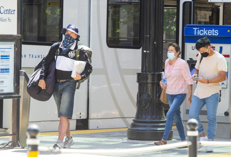 (Rick Egan | Tribune file photo) Pedestrians wear masks as they exit a TRAX train, in downtown Salt Lake City, Aug. 13, 2020.