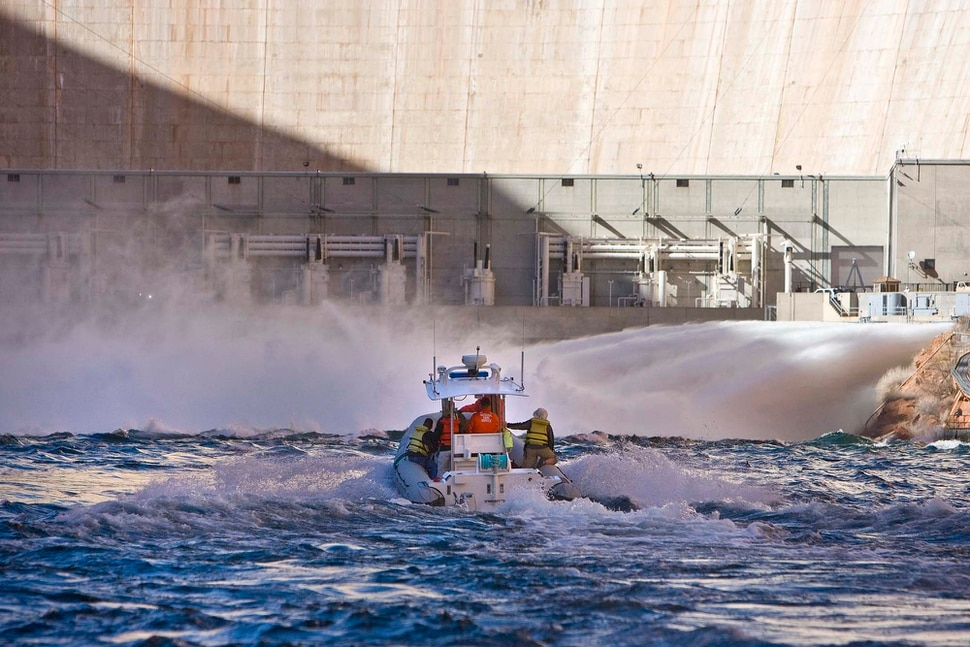 (Tribune file photo) A Park Service boat approaches the base of the Glen Canyon Dam where water surged into the Colorado River in 2008, as part of an ongoing experiment to see if a springtime influx of more water would improve fisheries downstream. The Lake Powell Pipeline would draw water from the river at Lake Powell, behind Glen Canyon dam, and pump it some 140 miles north and west for delivery to homes and businesses in St. George and other Utah communities.