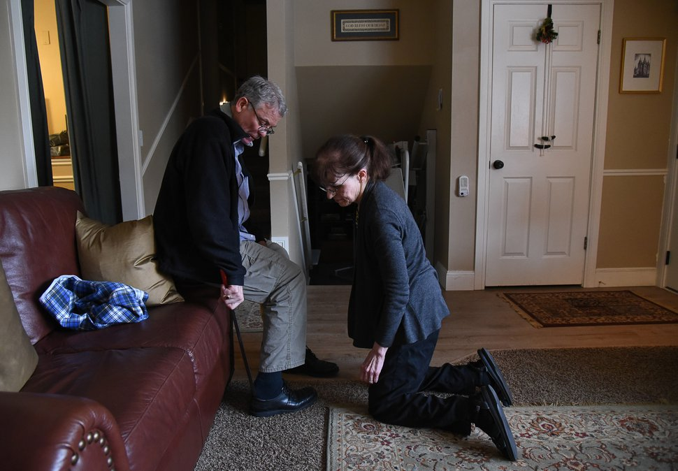 (Francisco Kjolseth | The Salt Lake Tribune) Mark Sargeant uses a long shoehorn to put on his shoes with the help of his wife, Rosie, at their Orem home. Mark does everything his body will allow but has faced endless disruptions and challenges as his ALS progresses and Rosie has taken on the excruciating role of caregiver.