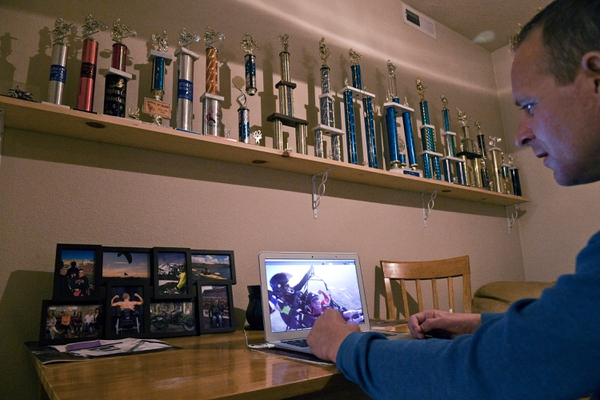 Sam Jolley watches old footage of himself tandem paragliding as trophies from his motocross career sit on a shelf Friday, Dec. 22, 2017, at his home in Pleasant Grove, Utah.