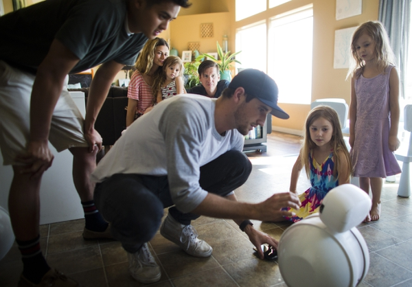 The Riner family watches as Jared Workman tests out Benni, a robot designed to interact with children on the autism spectrum, at the Riner family home in Draper, Friday, July 13, 2018. (Evan Cobb/The Daily Herald via AP)