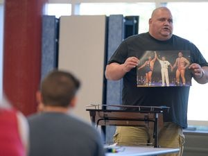 (Francisco Kjolseth     The Salt Lake Tribune file photo )  Olympic wrestling champion Rulon Gardner displays a photo of his historic upset over Russian Aleksandr Karelin for the gold medal during the 2000 Sydney Olympics as he meets with students and parents on Wed. May 16, 2018, to introduce himself as the new wrestling coach at Herriman High school.
