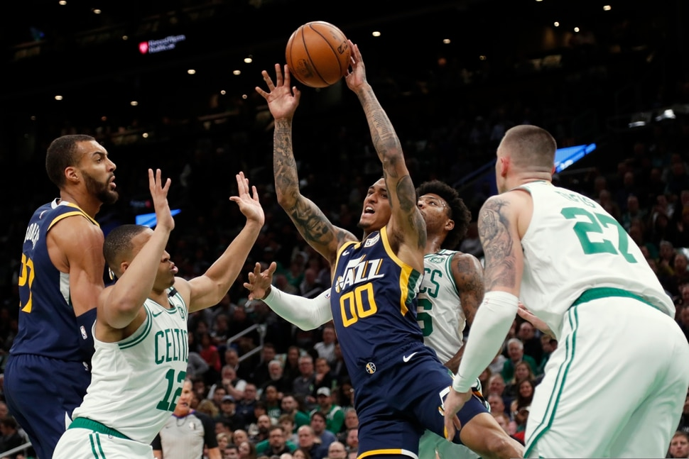 Utah Jazz's Jordan Clarkson (00) passes the ball off in traffic during the first quarter of an NBA basketball game against the Boston Celtics, Friday, March 6, 2020, in Boston. (AP Photo/Winslow Townson)