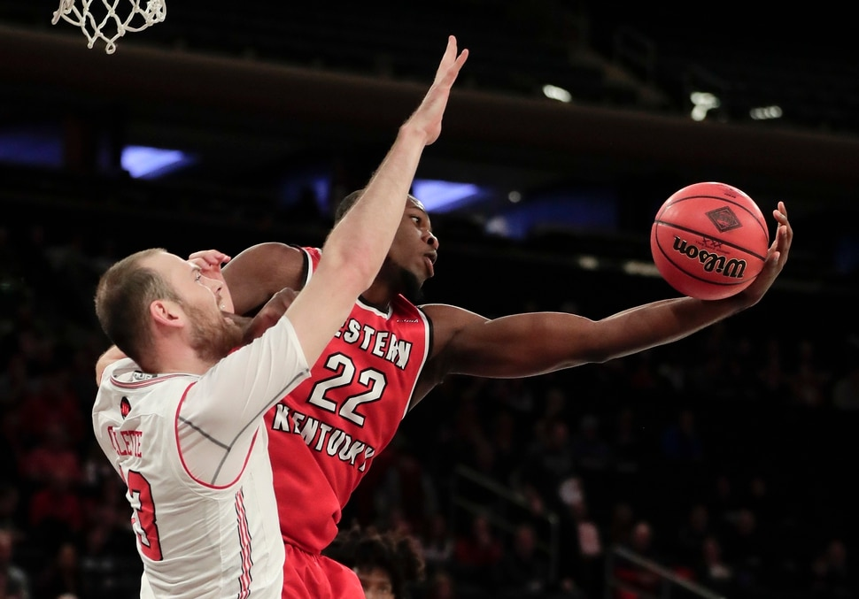 Western Kentucky forward Dwight Coleby (22) pulls down a rebound against Utah forward David Collette (13) during the first half of an NCAA college basketball game in the semifinals of the NIT, Tuesday, March 27, 2018, in New York. (AP Photo/Julie Jacobson)