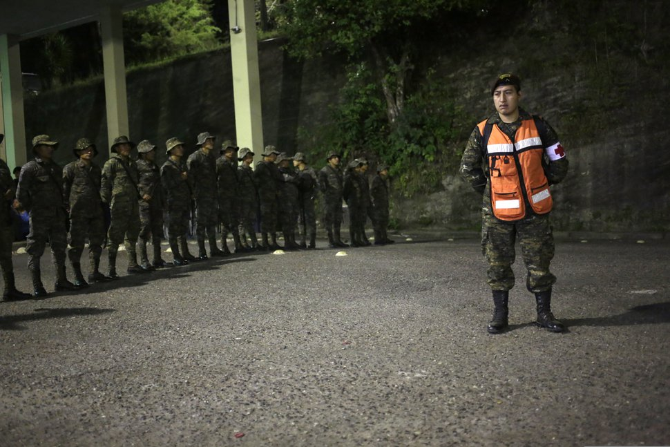 Soldiers stand guard as Honduran migrants enters Guatemala, at the border crossing in Agua Caliente, Guatemala, Tuesday, Jan. 15, 2019. The latest caravan of Honduran migrants hoping to reach the U.S. has crossed peacefully into Guatemala, under the watchful eyes of about 200 Guatemalan police and soldiers. (AP Photo/Moises Castillo)