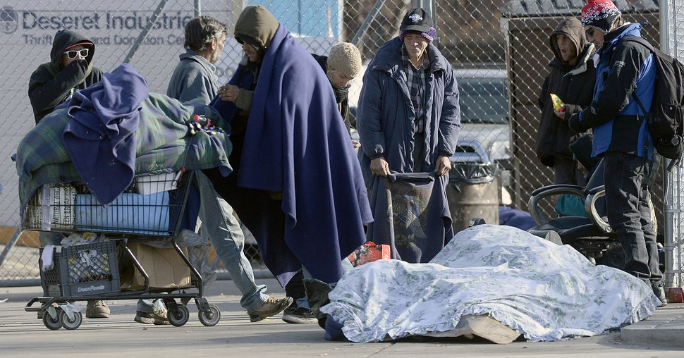 (Al Hartmann | Tribune file photo) Homeless people gather on 500 West near the Road Home shelter on Dec. 7, 2016.