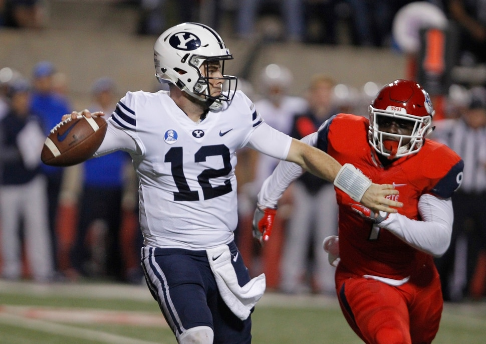 BYU's Tanner Mangum tries to complete a pass as Fresno State's Jeffrey Allison chases during the first half of an NCAA college football game in Fresno, Calif., Saturday, Nov. 4, 2017. (AP Photo/Gary Kazanjian)