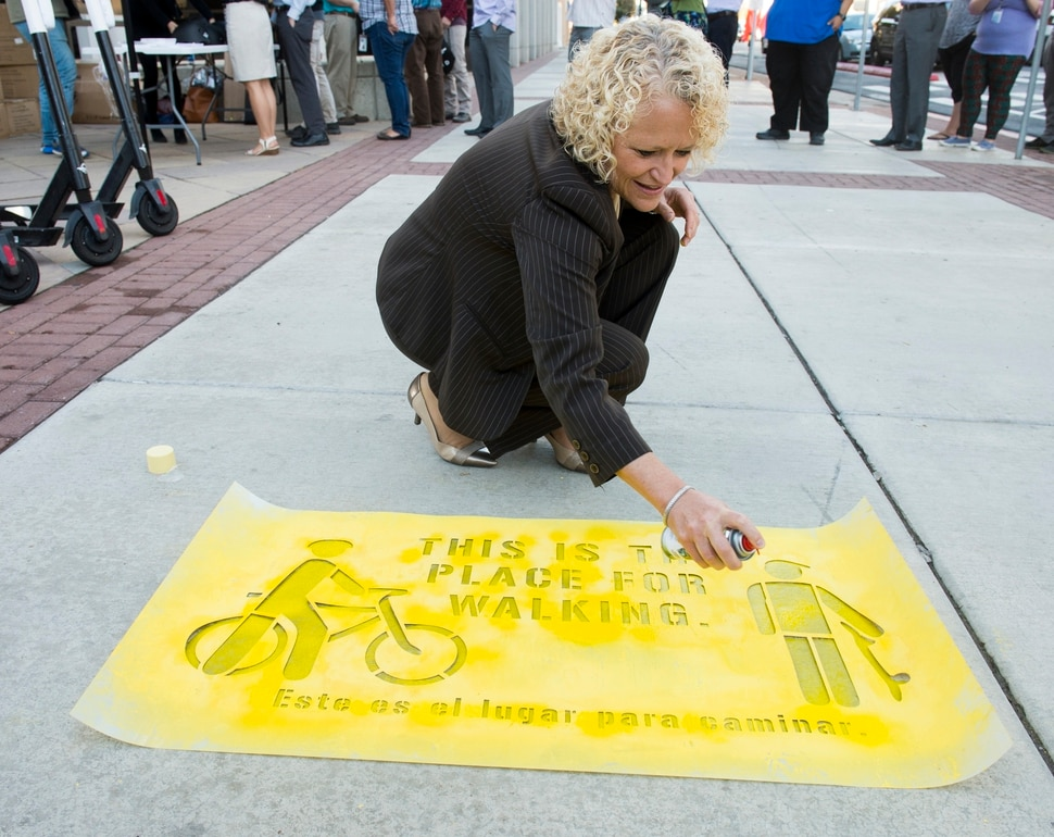 (Rick Egan | The Salt Lake Tribune) Salt Lake City mayor Jackie Biskupski painted a sidewalk stencil, as Salt Lake City launches a new campaign with e-scooter companies Lime and Bird in an effort to help residents and visitors understand the rules of the sidewalk, Wednesday, Oct. 3, 2018.