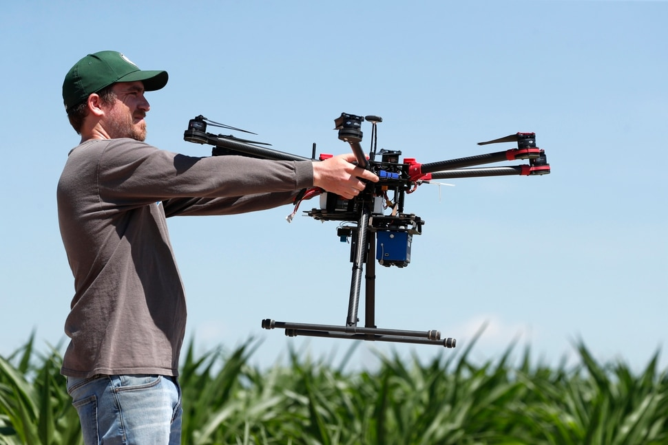 (David Zalubowski   AP Photo) In this Thursday, July 11, 2019, photograph, United States Department of Agriculture intern Alex Olsen prepares to place down a drone at a research farm northeast of Greeley, Colo. Researchers are using drones carrying imaging cameras over the fields in conjunction with stationary sensors connected to the internet to chart the growth of crops in an effort to integrate new technology into the age-old skill of farming.