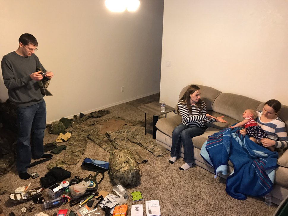 (Nate Carlisle | The Salt Lake Tribune) Jesse Raynor displays the military gear he purchased while his two wives, Amber Raynor (left) and Shelby Thompson, sit in their home near Sandpoint, Idaho, on Jan. 12, 2019. Shelby's 18-month-old daughter, Nikita, is crawling on her mother's lap. The family once worshipped in the Utah-based Apostolic United Brethren, where Jesse Raynor says he was recruited in 2011 into what he describes as a militia.