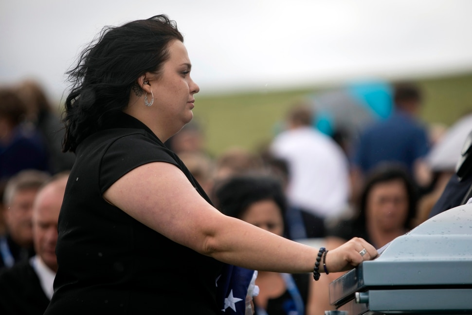 (Ben Dorger/Standard-Examiner via AP)Ashley Lyday, the wife of Ogden Police Officer Nate Lyday, pauses over her husband's remains at Lindquist's Memorial Gardens of the Wasatch cemetery, on Saturday, June 6, 2020, in Ogden, Utah. The 24-year-old officer was shot and killed last Thursday, May 28, when responding to a domestic violence call.