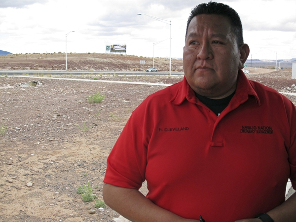 This Thursday, May 3, 2018 photo shows Harland Cleveland of the Navajo Nation Department of Emergency Management talking about efforts to bury dozens of horses that died after becoming trapped in a muddy watering hole near Cameron, Ariz. A couple of miles off the highway through northern Arizona is one of the most stark examples of the toll drought has taken on the region: more than 100 dead horses surrounding by cracked dirt, swirling dust and a ribbon of water that couldn't quench their thirst. Officials on the Navajo Nation are working to cover the site with lime to help the animals decompose and keep away scavengers. (AP Photo/Felicia Fonseca)