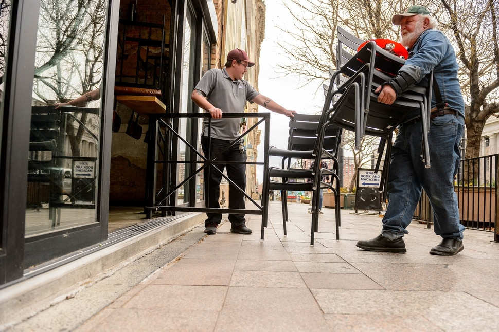 (Trent Nelson | The Salt Lake Tribune) Dylan Ewell and Patrick Liley pack up chairs as White Horse Restaurant and Bar prepares to close for 30 days, in Salt Lake City on Monday, March 16, 2020.