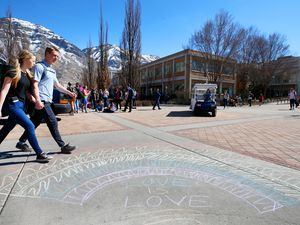 (George Frey | Special to The Tribune) Two students hold hands as they walk past other BYU students in front of the Ernest L. Wilkinson Student Center on the campus of Brigham Young University to protest BYU's rollback of a newly announced policy change on LGBTQ students on March 5, 2020, in Provo.