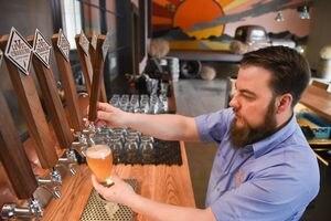 (Francisco Kjolseth  |  The Salt Lake Tribune)  Chris Detrick, head brewer for Level Crossing Brewing Co. pours beer on tap.