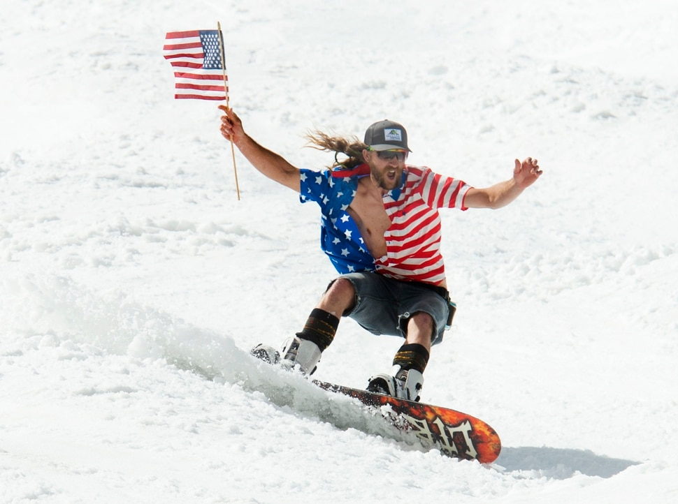 (Rick Egan | The Salt Lake Tribune) James Perry, from Salt Lake City, makes his way down the hill while waving a flag and dressed for the Fourth of July on the last ski day of the year at Snowbird Ski resort on Thursday, July 4, 2019.