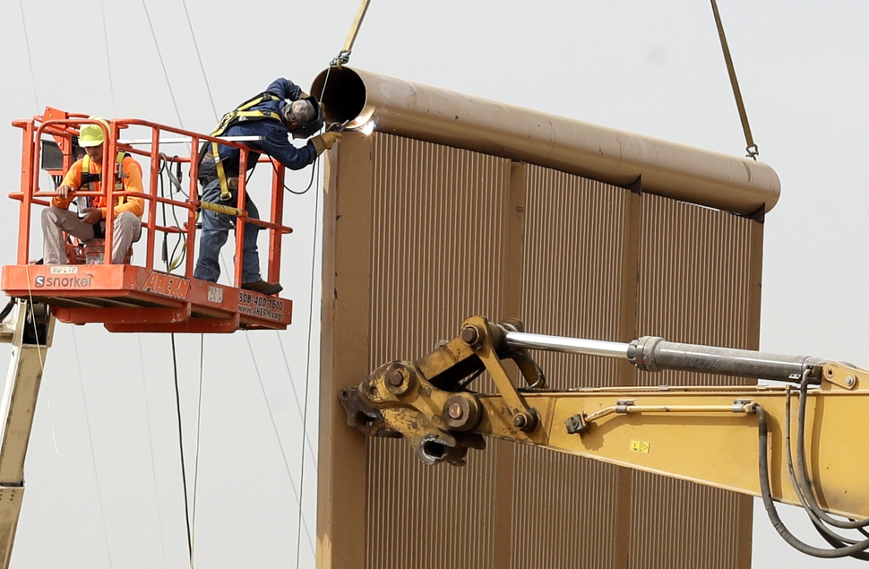 (Gregory Bull | Associated Press file photo) In this Oct. 19, 2017 file photo, crews work on a border wall prototypes near the border with Tijuana, Mexico, in San Diego. A U.S. official says recent testing of prototypes of President Donald Trump's proposed wall with Mexico found their heights should stop border crossers. U.S. tactical teams spent three weeks trying to breach and scale the models in San Diego. An official with direct knowledge of the results said they point to see-through steel barriers topped by concrete as the best design. The official spoke to The Associated Press on condition of anonymity because the information is not authorized for release.