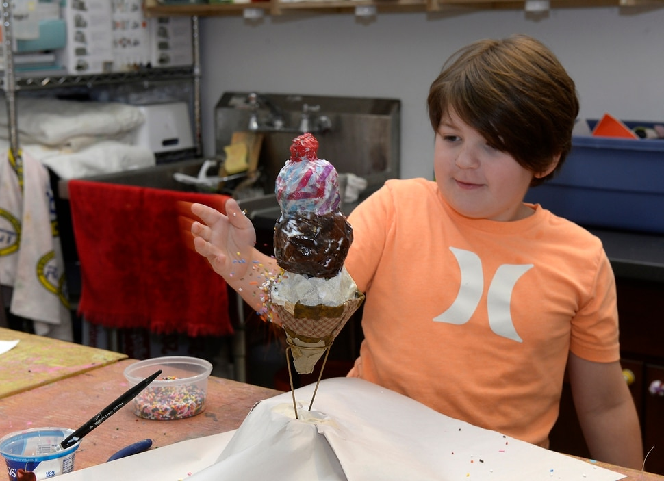 (Al Hartmann | The Salt Lake Tribune) Memphis Black, 8, puts on sprinkles to his paper mache ice cream delight creation at the Clever Octopus a creative reuse center in Murray . The shop that hosts workshops and camps for kids to engage in artistic activities using recycled arts and crafts materials. August 17, 2017.
