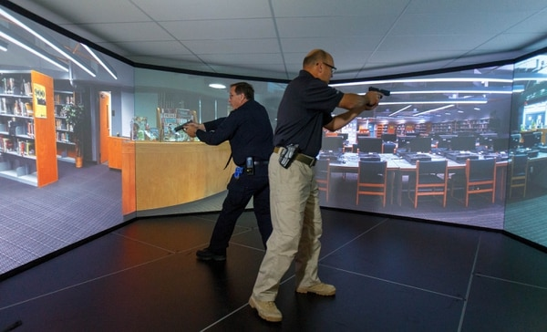 Trent Nelson | The Salt Lake Tribune Unified Police Deputy Chief Shane Hudson, right, and Range Master Nick Roberts run through a school shooting simulation while demonstrating a new five-screen training simulator used to put officers through realistic situations in Salt Lake City on Thursday, Nov. 7, 2013.
