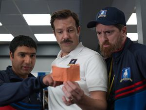 """This image released by Apple TV Plus shows Nick Mohammed, from left, Jason Sudeikis, and Brendan Hunt in """"Ted Lasso."""" The show was nominated for a Golden Globe for best musical or comedy series on Wednesday, Feb. 3, 2021. Sudeikis was also nominated for best actor in a musical/comedy series. (Apple TV Plus via AP)"""