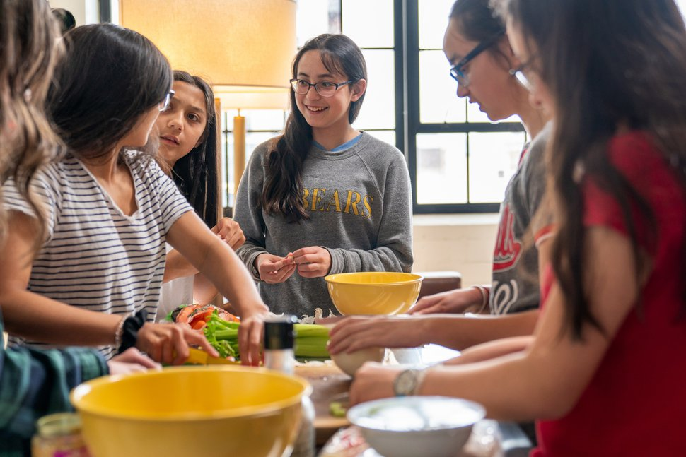 (Photo courtesy of The Church of Jesus Christ of Latter-day Saints) Young Women in Ohio cook together. The church's new program for children and youths encourages personal development through gospel learning, service, activities and personal development.
