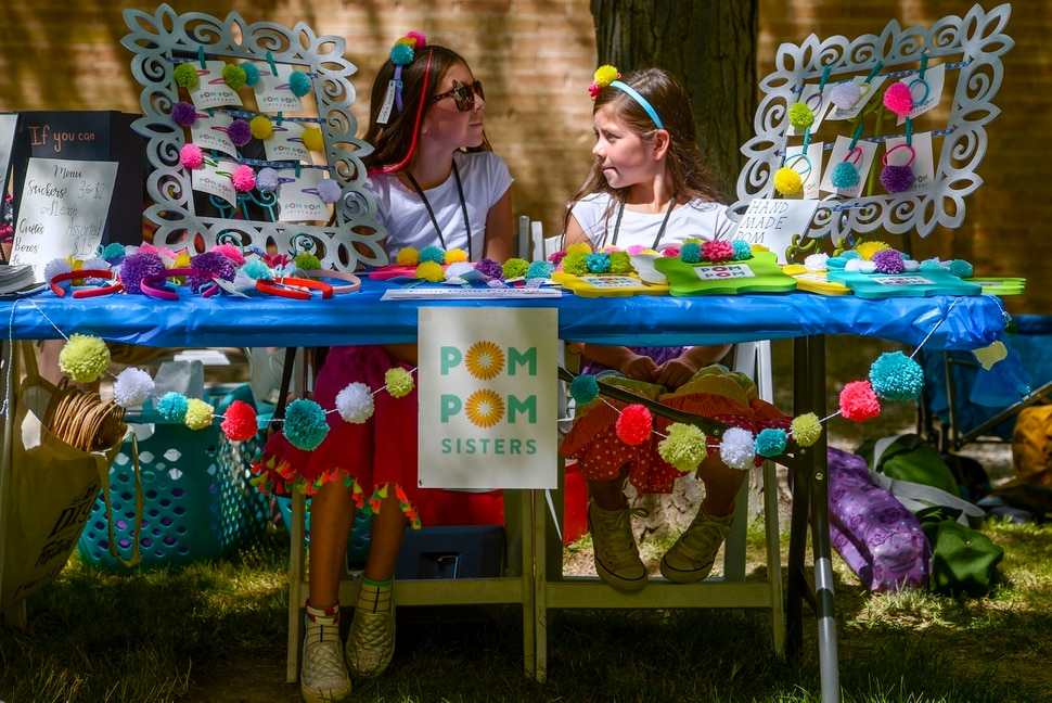 (Leah Hogsten | The Salt Lake Tribune) l-r The Pom Pom sisters Evi and Syrri Bateman peddle hair barrettes, headbands, picture frames and ponytail holders decorated with pom poms at the Craft Lake City DIY Festival Kid Row, where children 14 and under make and sell their products. Craft Lake CityÕs DIY Festival is UtahÕs largest local, three day arts festival with over 300 artisans, DIY engineers, vintage vendors and craft food creators.