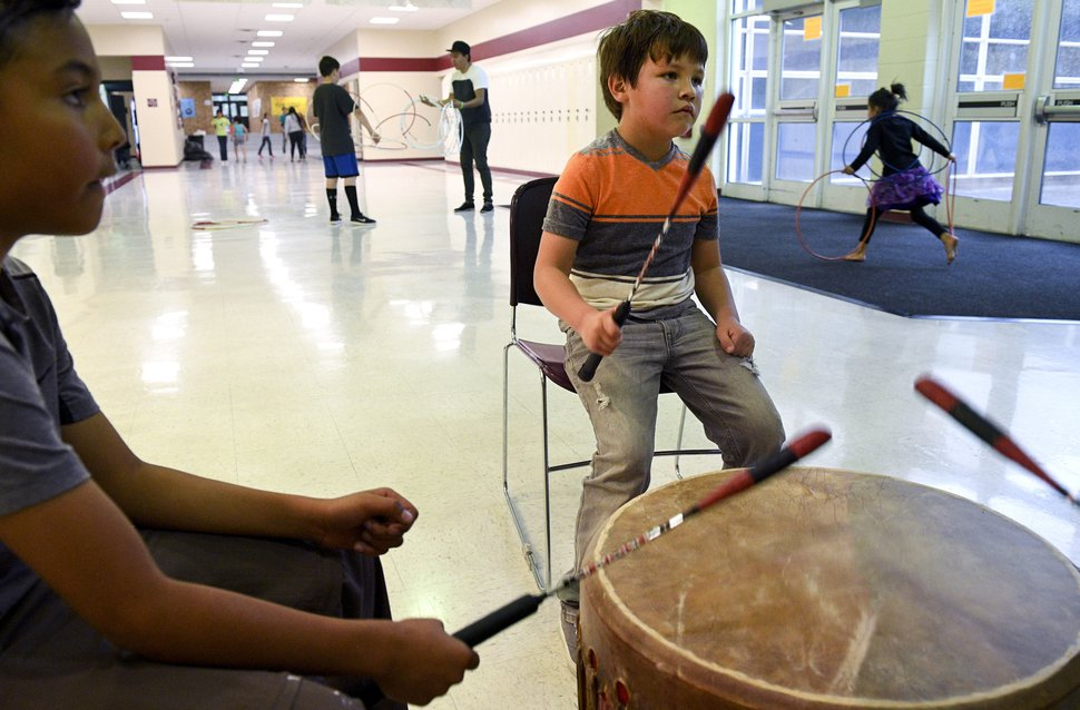 Rushton Beagley, 6, center, and Israel Youngbull, 7, drum along with Jacob Crane, not pictured, a drumming and sining instructor, during classes held by Alpine School District's Title VI American Indian Education program Wednesday, May 2, 2018, at Mountain View High School in Orem, Utah. The program aims to promote academic productivity in raising test scores and graduation rates. (Isaac Hale /The Daily Herald via AP)