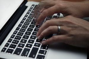 (Elise Amendola | AP file photo) This June 19, 2017, file photo shows a person working on a laptop in North Andover, Mass. The Utah Senate gave unanimous approval Wednesday to a bill that would make impersonating someone online without their consent and with the intent to do harm illegal.