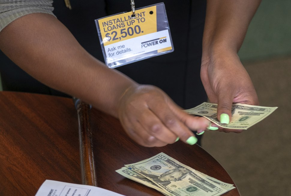In this Aug. 9, 2018, photo, a manager of a financial services store in Ballwin, Mo., counts cash being paid to a client as part of a loan. The firm offers cash-based financial services, including payday loans, installment loans, fund transfers and other financial services. (AP Photo/Sid Hastings)